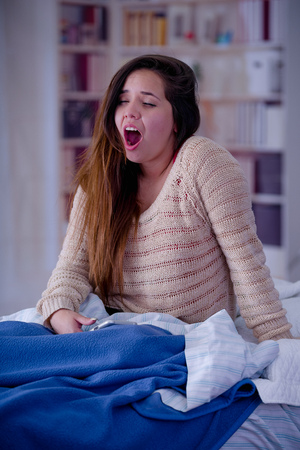 Close up of young woman with sleeplessness sitting on the bed yawning and trying to sleep, insomnia concept