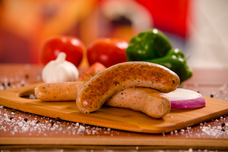 Close up of delicious grilled sausages and vegetables, tomato, onio, green pepper and rosemary spices on a wooden background in rustic style
