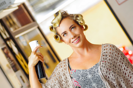 Close-up of young woman fixing hairstyle with hair spray in hairdressing beauty salon