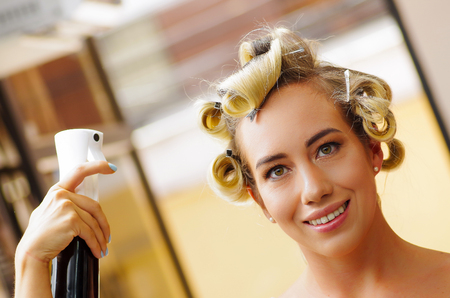 Close up of young woman fixing hairstyle with hair spray in hairdressing beauty salon, in a blurred background 写真素材