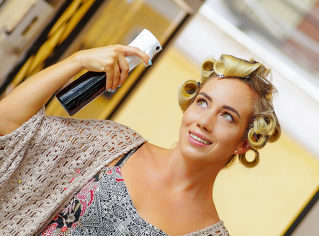 Close up of young blonde woman fixing hairstyle with hair spray in hairdressing beauty salon, in a blurred background