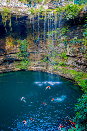 CHICHEN ITZA, MEXICO - NOVEMBER 12, 2017: Unidentified people swimming at Ik-Kil Cenote near Chichen Itza, Mexico. Lovely cenote with transparent waters and hanging roots