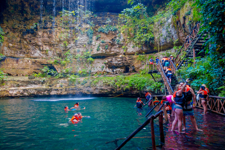 CHICHEN ITZA, MEXICO - NOVEMBER 12, 2017: Unidentified people taking pictures at beautiful Ik-Kil Cenote pond with many people swimming, near Chichen Itza in Mexico