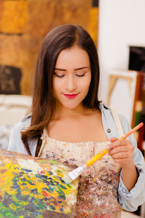 Beautiful young woman painter with color palette and paint brush in hand, in a blurred background