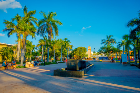 COZUMEL, MEXICO - NOVEMBER 09, 2017: Unidentified people walking and sitting in a public chairs in a park in enjoying the day in a park of Cozumel