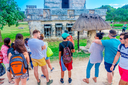 TULUM, MEXICO - JANUARY 10, 2018: Unidentified tourists walking and enjoying the view of Temple of the Frescoes at the Mayan ruins of Tulum in Quintana Roo,Yucatan Peninsula, Mexico Editorial
