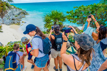 TULUM, MEXICO - JANUARY 10, 2018: Unidentified people in the cliff taking pictures and enjoying the beautiful view close to the Mayan Ruins of Tulum Besides Caribbean Sea. Riviera Maya, Traveling America Editorial