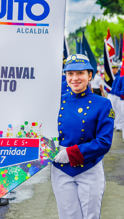 Quito, Ecuador - January 31, 2018: Portrait of unidentifed woman wearing a blue uniform of Liceo naval, holding a informative banner and walking during a parade in Quito, Ecuador