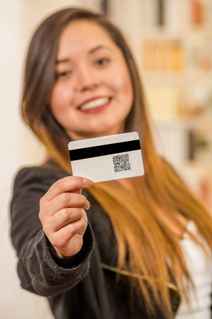 Close up of a beautiful smiling womans showing business card with QR code information in a blurred background