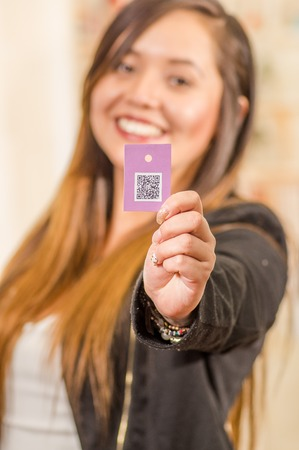 Close up of beautiful young woman showing a clothes ticket with QR code information, in a blurred background Stock Photo