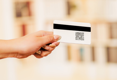 Close up of a woman s hand showing business card with QR code information in a blurred background