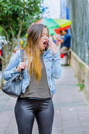 Fashion trendy casual young woman walking in the streets and yawning during a long day, wearing a jean jacket and black leggings in a blurred background