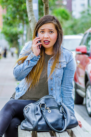 Fashion trendy casual young woman wearing a jean jacket and black leggings, using her cellphone and showing shock emotion. Female portrait with shocked facial expression
