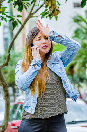 Fashion trendy casual young woman wearing a jean jacket and black leggings, using her cellphone and showing shock emotion with her hand in the head. Female portrait with shocked facial expression Stock Photo