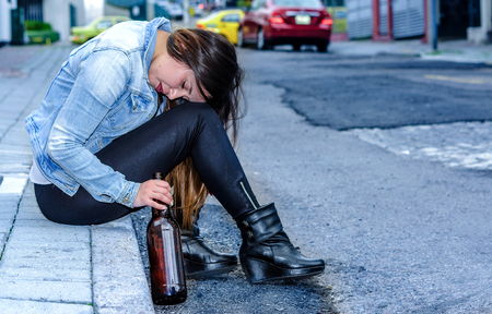 Beautiful young drunk woman sitting in a sidewalk with bottle of beer in her hand sleeping outdoor, desesperate woman and addict concept Stock Photo