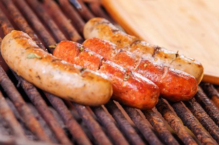 Close up of three grilling sausages on barbecue grill. BBQ in the garden. Bavarian sausages Stock Photo
