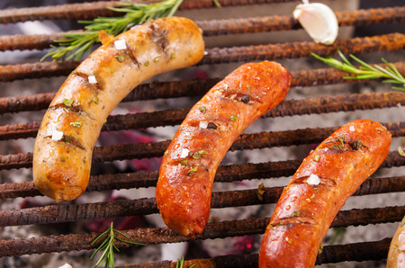 Close up of three grilling sausages on barbecue grill with some species. BBQ in the garden. Bavarian sausages