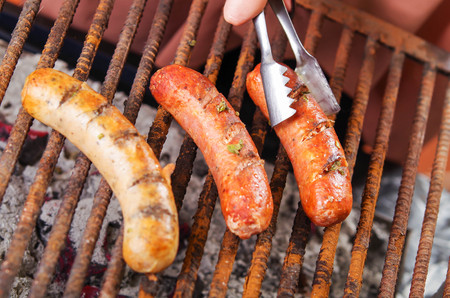 Close up of woman s hand holding a tongs turning the grilling sausages on barbecue grill. BBQ. Bavarian sausages Stock Photo