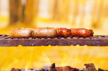 Close up of four grilling sausages on barbecue grill. BBQ in the garden. Bavarian sausages in a blurred background