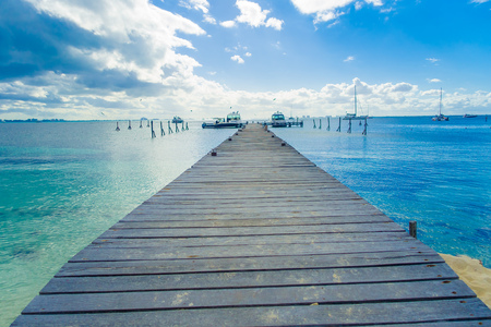 Outdoor view of a wooden dock into blue tropical sea in Isla Mujeres, Yucatan Mexico Stock Photo