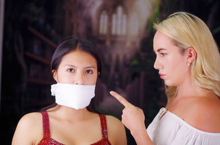 Young mad american blonde woman, exhorting to a latin woman to leave the country, using her hand and pointing to her, while foreign woman is with a white thing covering her mouth, racism, violence or discrimination concept Stock Photo