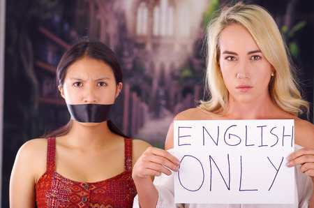 Young mad american blonde woman holding a piece of paper with a description of english only, while latin is with a black tape in her mouth, racism, violence or discrimination concept