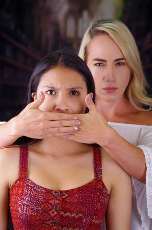 Young mad american blonde woman, covering with both hands the mouth of a foreign woman. Racism, violence or discrimination concept in a blurred background Stock Photo
