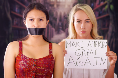 Young mad american blonde woman holding a piece of paper with a description of make america great again, while latin is with a black tape in her mouth, racism, violence or discrimination concept