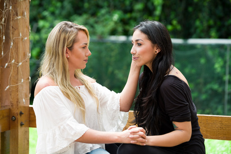 A pair of proud lesbian sitting in outdoors looking at each other and go kissing in a garden background