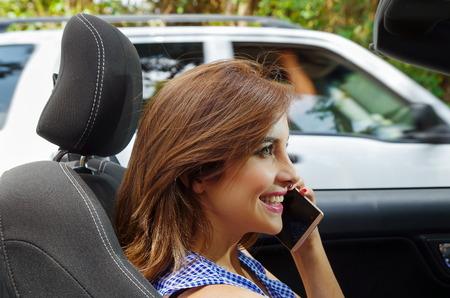 Portrait of beautiful woman using her cellphone inside of the black car, while she is driving in a blurred nature background