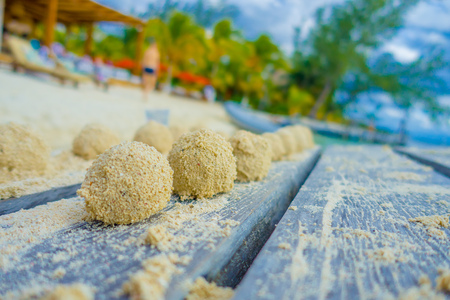 Close up of selective focus of small balls of sand after crabs lunch over a wooden structure in the beach of isla mujeres in Mexico