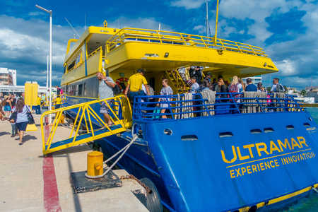 ISLA MUJERES, MEXICO, JANUARY 10, 2018: Unidentified people boarding a huge boat of color blue and yellow to visit the Isla Mujeres. The island is some 7 kilometres long and 650 metres wide