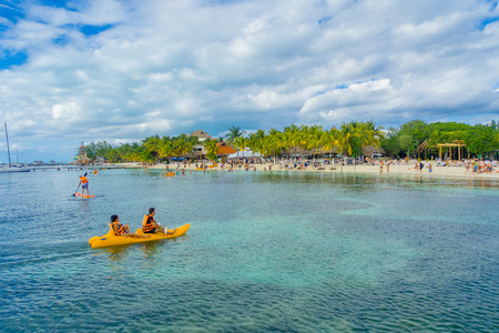 CANCUN, MEXICO - JANUARY 10, 2018: Unidentified people paddling in their kayack in a beautiful caribbean beach isla mujeres with clean and transparent water in Mexico, sun and palms. Tourism concept Editorial