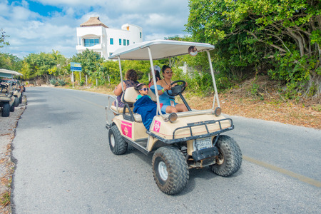 ISLA MUJERES - JANUARY 10, 2018: Outdoor view of unidentified woman riding a mountain vehicle in the streets of the city close to Isla Mujeres, Mexico Editorial