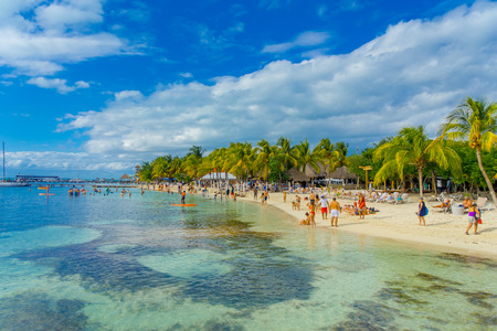 CANCUN, MEXICO - JANUARY 10, 2018: Unidentified people swimming in a beautiful caribbean beach isla mujeres with clean water in Mexico, paradise island, sun and palms. Tourism concept Editorial
