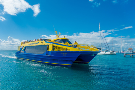 CANCUN, MEXICO - JANUARY 10, 2018: Unidentified people enjoying the view of the Isla Mujeres, in a huge boat of color blue and yellow. The island is some 7 kilometres long and 650 metres wide Editorial