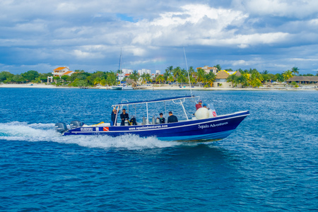 CANCUN, MEXICO - JANUARY 10, 2018: Unidentified people sailing in a yatch Outdoor view of huge boat of color blue and yellow sailing in the waters close tothe Isla Mujeres Editorial
