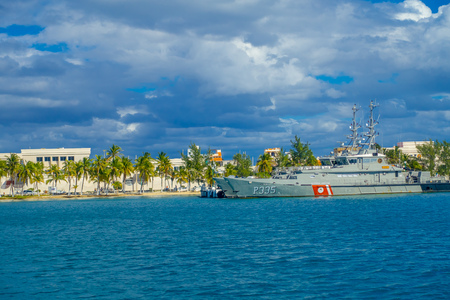 ISLA MUJERES, MEXICO, JANUARY 10, 2018: Beautiful outdoor view of military ship with some buildings in the horizont in the beach Isla Mujeres in caribbean sea, with a turquoise water in Mexico Editorial