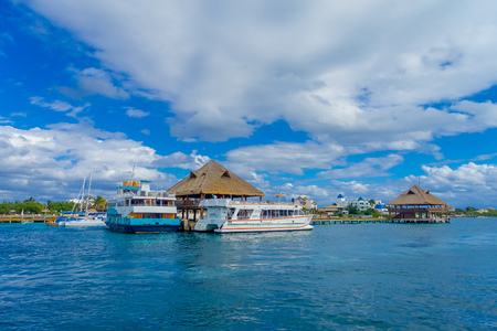 ISLA MUJERES, MEXICO, JANUARY 10, 2018: Outdoor view of ship in the shore with many passenger, close to a typical house from the Isla Mujeres . The island is some 7 kilometres long and 650 metres wide Editorial
