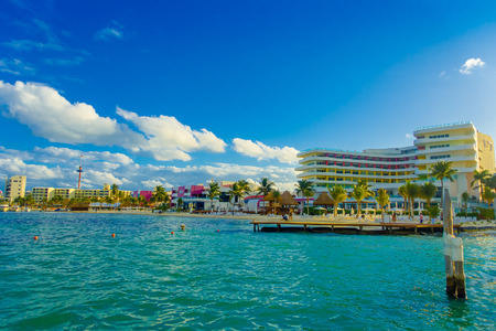 ISLA MUJERES, MEXICO, JANUARY 10, 2018: Outdoor view of some buildings in the horizont at the beach Isla Mujeres, with blue water in Mexico