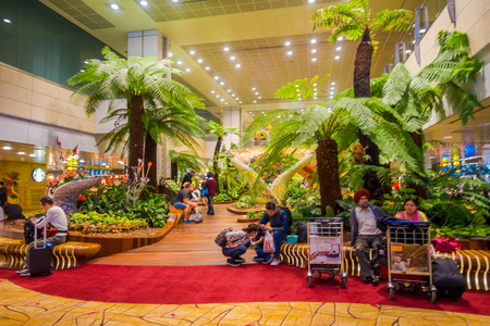 SINGAPORE, SINGAPORE - JANUARY 30, 2018: Indoor view of unidentified people sitting in a chairs in a small garden with plants inside of Singapore Changi Airport. Singapore Changi Airport is the primary civilian airport for Singapore