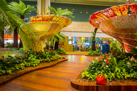 SINGAPORE - CIRCA AUGUST, 2016: Indoor view of people walking in a small garden with plants inside of Singapore Changi Airport. Singapore Changi Airport is the primary civilian airport for Singapore Editorial