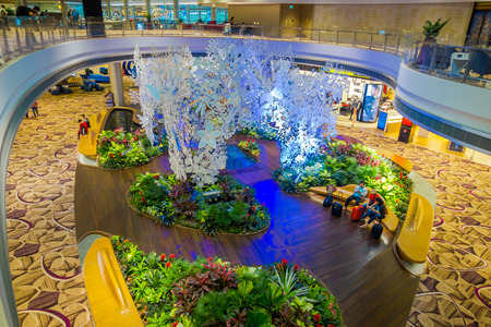 SINGAPORE - CIRCA AUGUST, 2016: Above view of unidentified people sitting in a chairs in a small garden with plants inside of Singapore Changi Airport. Singapore Changi Airport is the primary civilian airport for Singapore Editorial