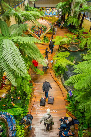 SINGAPORE, SINGAPORE - JANUARY 30, 2018: Above Indoor view of people walking in a small garden with plants inside of Singapore Changi Airport. Singapore Changi Airport is the primary civilian airport for Singapore