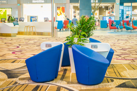 SINGAPORE, SINGAPORE - JANUARY 30, 2018: Indoor view of waiting lounge area with a blue sofa inside of Changi international airport