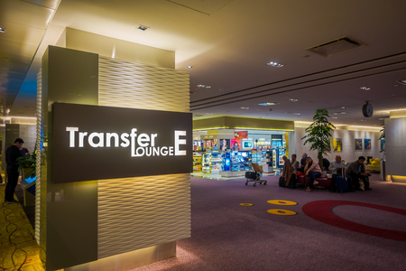 SINGAPORE, SINGAPORE - JANUARY 30, 2018: Close up of unidentified people sitting and waiting in a transfer lounge, with an informative sign in the wall in Singapore Changi Airport