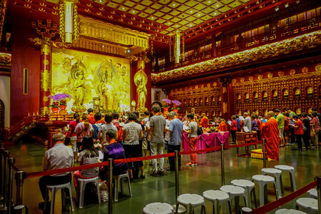 SINGAPORE, SINGAPORE - JANUARY 30. 2018: Unidentified people praying to the Lord buddha statue inside Buddha Tooth Relic temple ,Singapore near china town Editorial