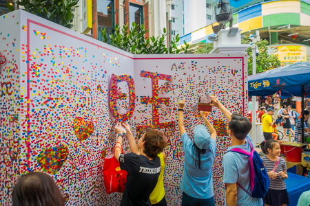 SINGAPORE, SINGAPORE - JANUARY 30. 2018: Outdoor view of young people taking pictures and putting some paper hearts over a white structure in The Lau Pa Sat festival market Telok Ayer used as a popular food court hawker center in Singapore Editorial