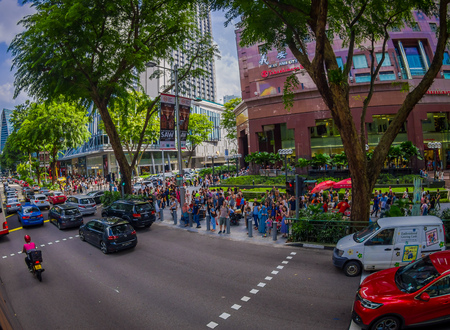 SINGAPORE, SINGAPORE - JANUARY 30. 2018: Outdoor view of crowd of people walking in the streets close to a heavy traffic in the streets of the city in a a public residential condominium buildings complex and downtown skylines at Kallang neighborhood in Si Editorial
