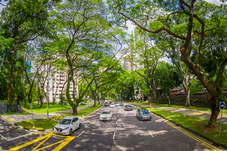 SINGAPORE, SINGAPORE - JANUARY 30. 2018: Beautiful outdoor view of many cars in a road surrounding of vegetation at public residential condominium building complex and downtown skylines at Kallang neighborhood in Singapore, fish eye effect Editorial